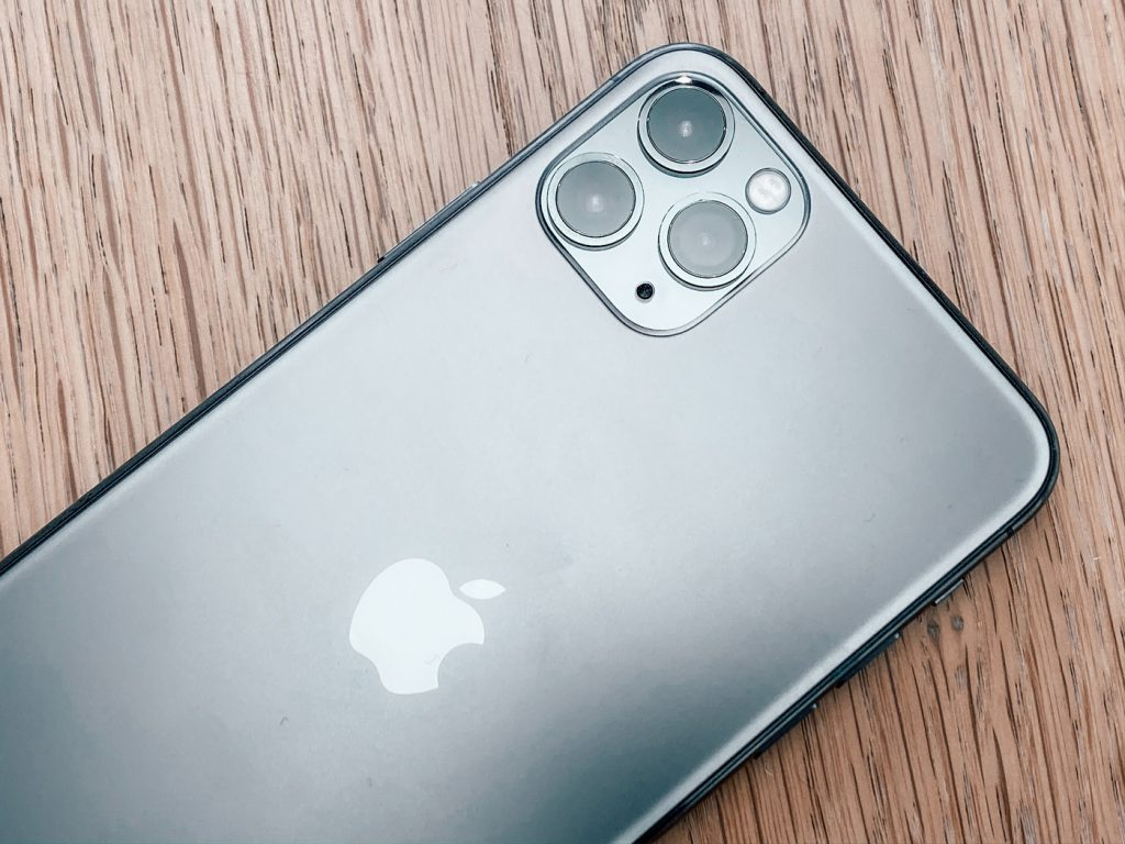 An iPhone 11 pro face down on a wooden table top