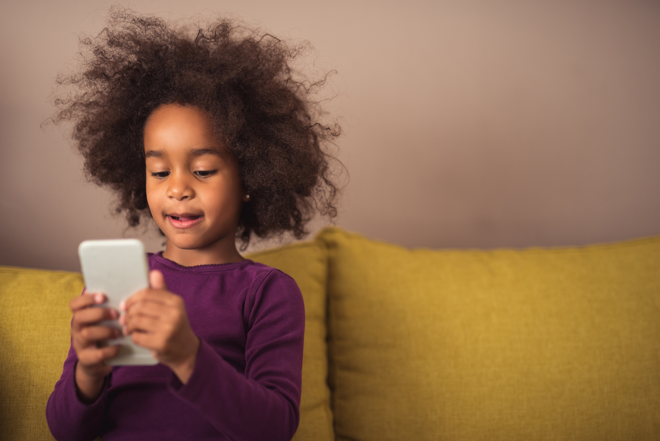 A child sitting on a sofa using a mobile phone