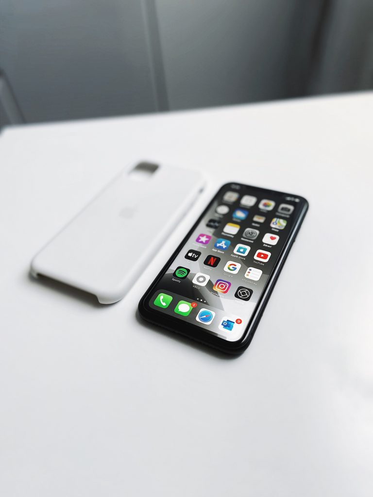 An iPhone laid face-up on a white desk next to a case