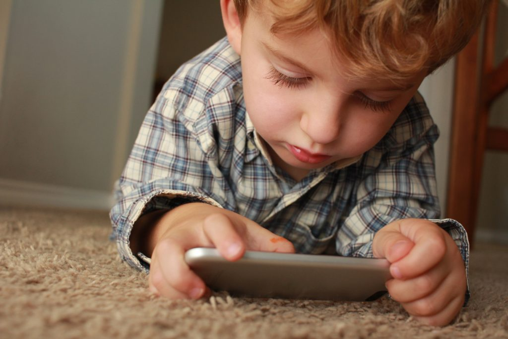 A child laying on the floor playing on a mobile phone
