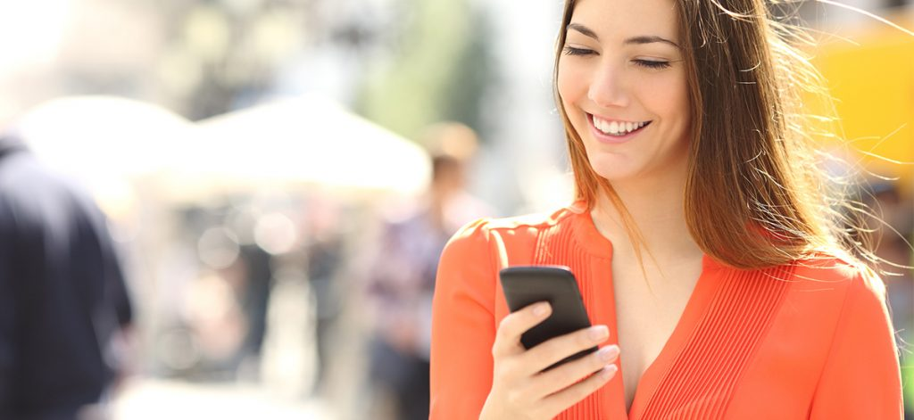 A woman smiling as she walks down a street looking at her mobile phone