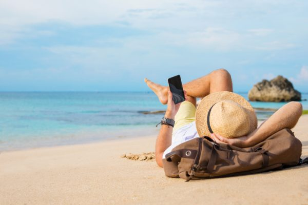 A man laying on a sandy beach using his mobile phone