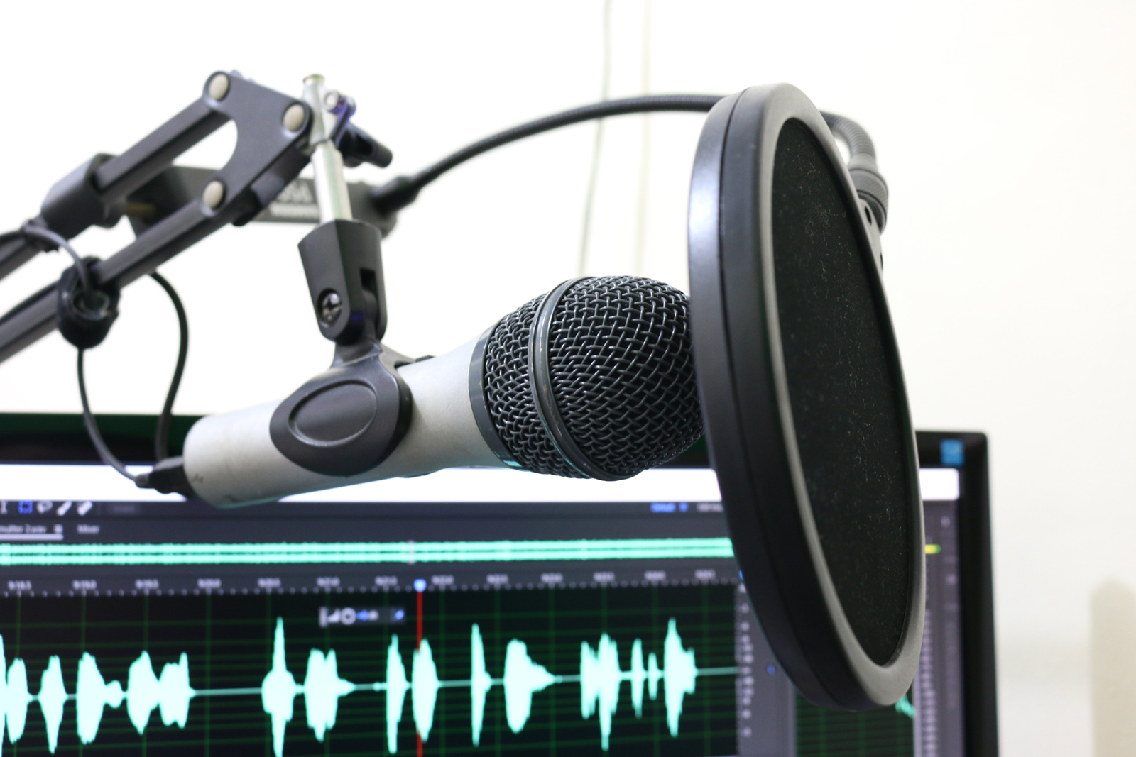 A podcast microphone set up with a screen receiving sound in the background