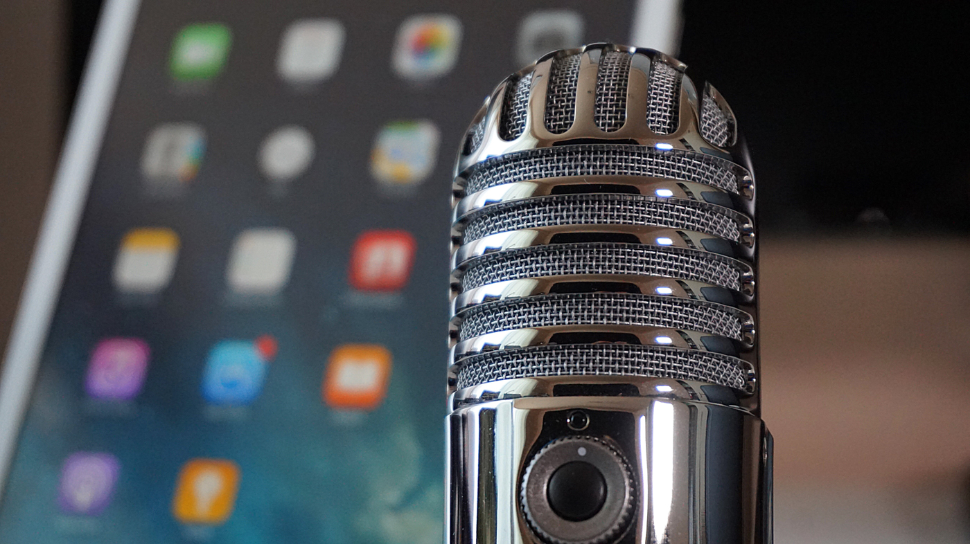 A microphone set up in-front of a tablet for a podcast