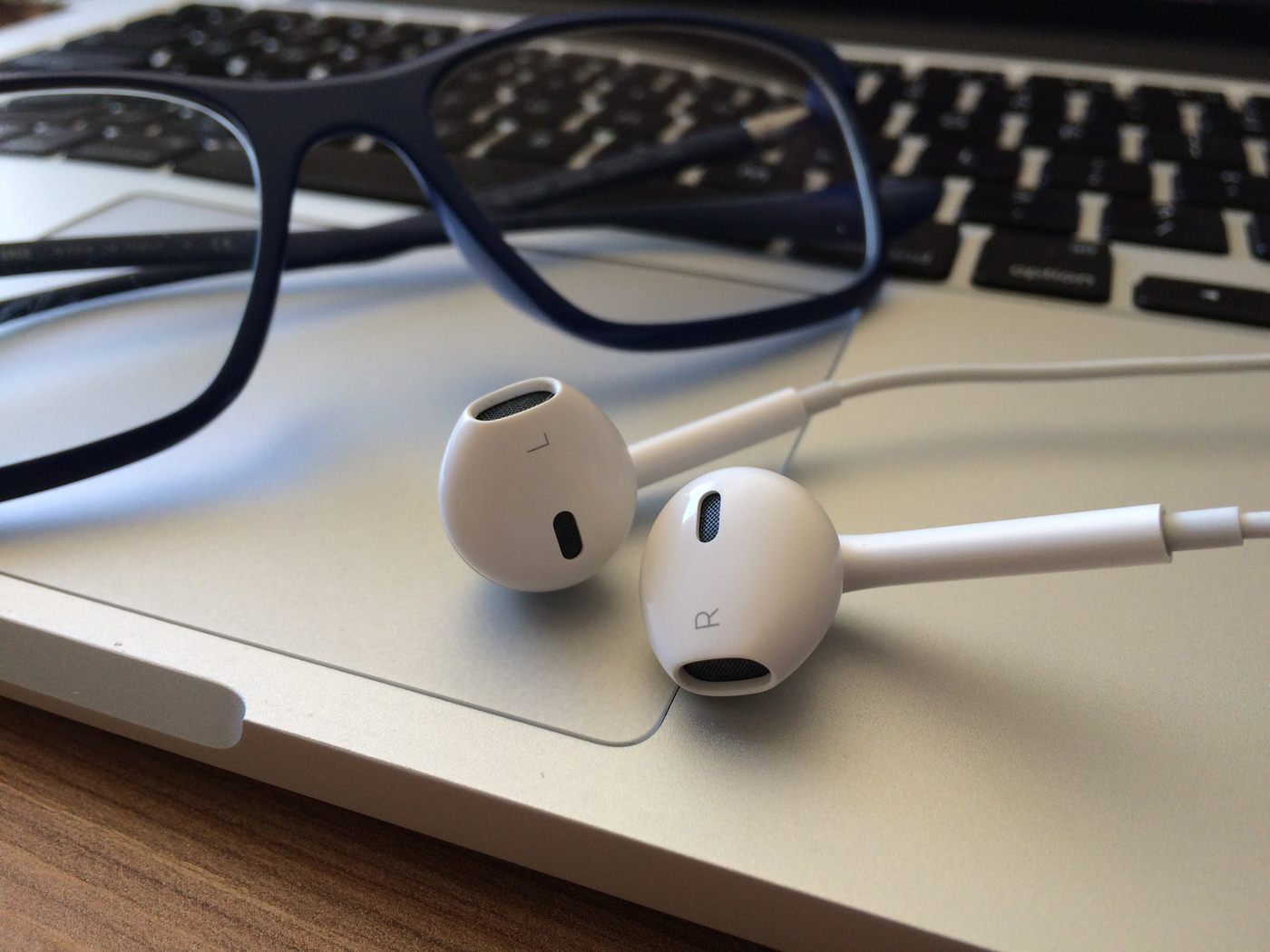 A pair of headphones resting on a laptop next to a pair of reading glasses