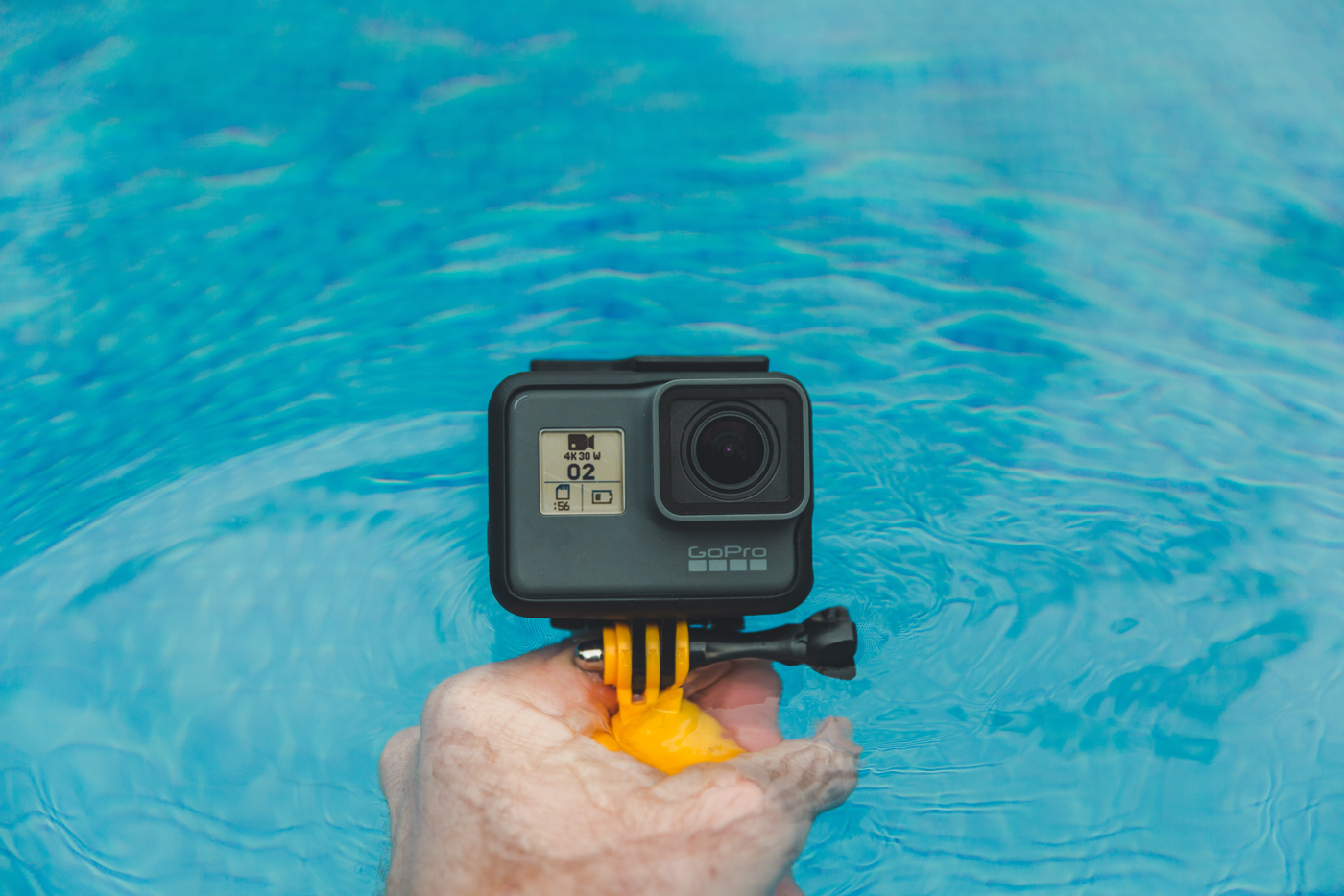 A GoPro on a stand about to be submerged in water