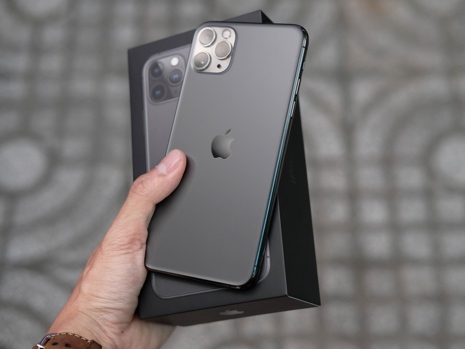 A person holding an iPhone 11 Pro Max ad its box