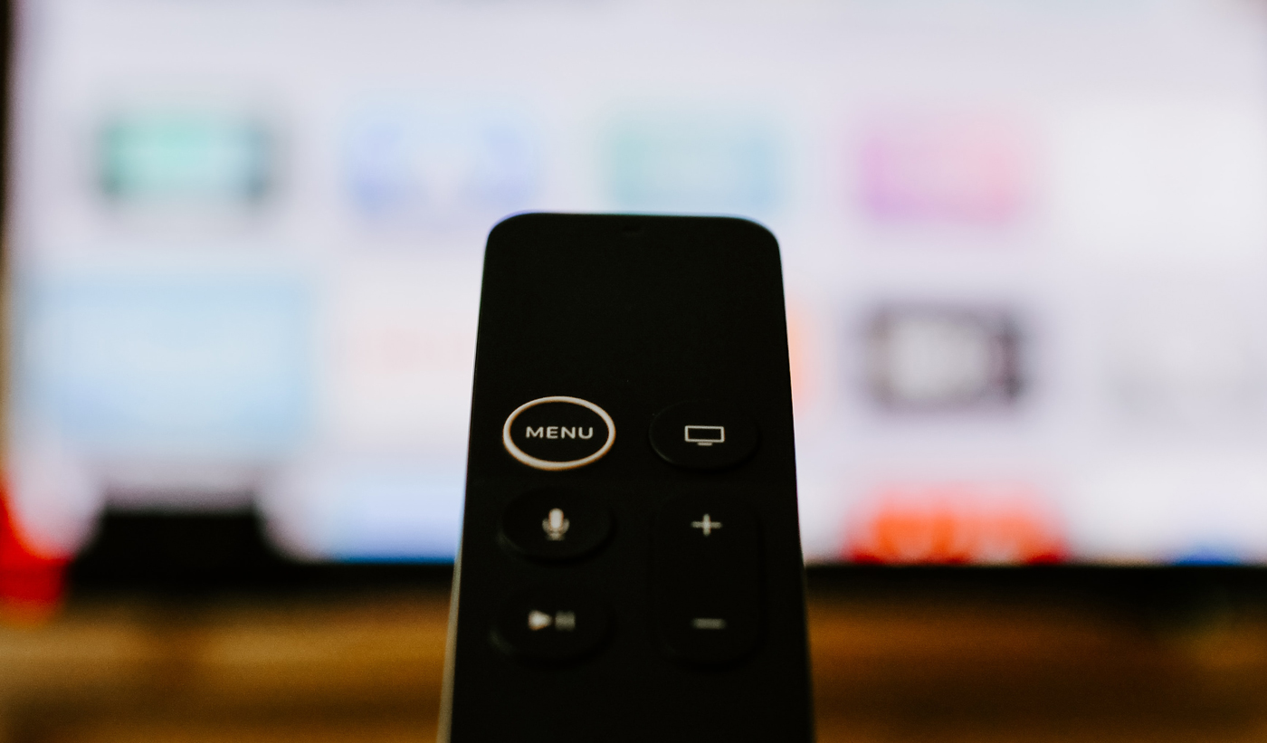 An Apple TV remote held up in-front of a TV with the Apple TV home page on
