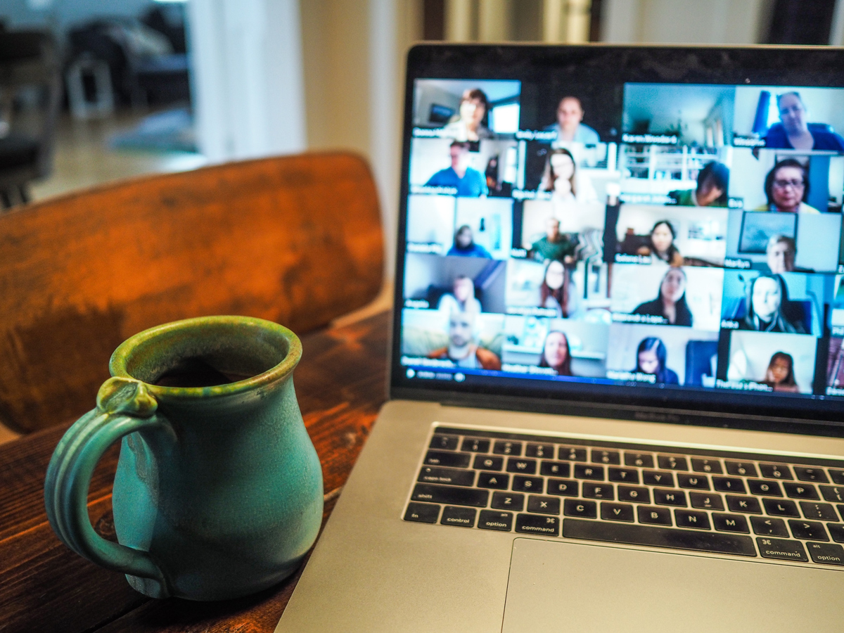 A laptop with a Zoom meeting taking place on screen with a mug of coffee next to it