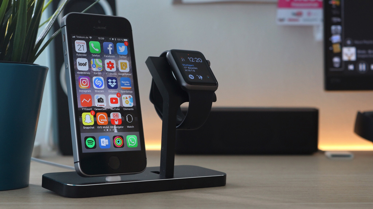 An iPhone and iWatch placed on a stand on a desk