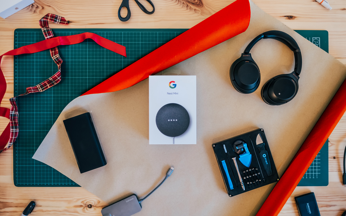 A Google Nest Mini on a table about to be wrapped in wrapping paper with other gadget gifts